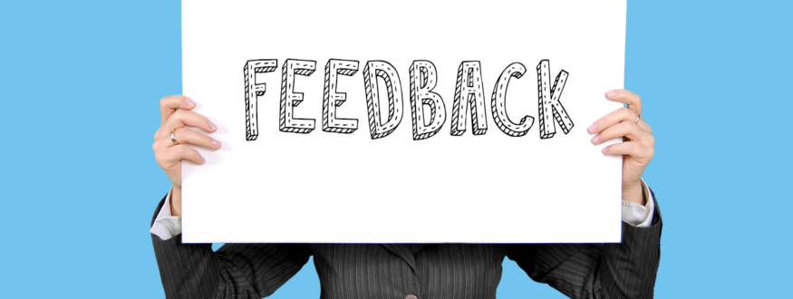 Employee holding up a placard with the word 'Feedback'