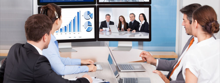 Image of employees reviewing performance on a computer screen